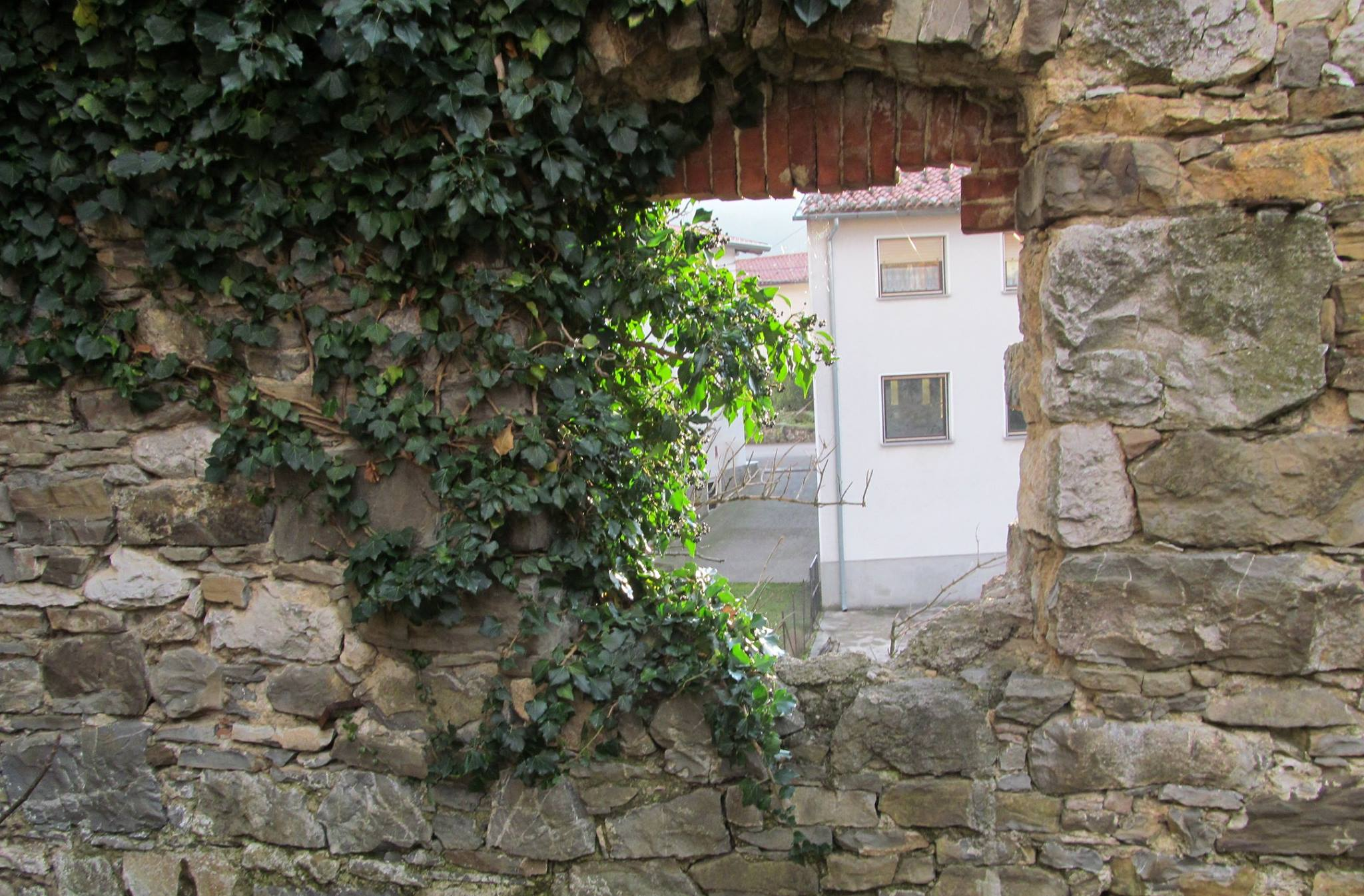 pogled_ skozi_ kamnite_ ostanke_ zidu_simbolna_povezava_z_vrtovcem_v_rojstni_kraj_slovenske_himne